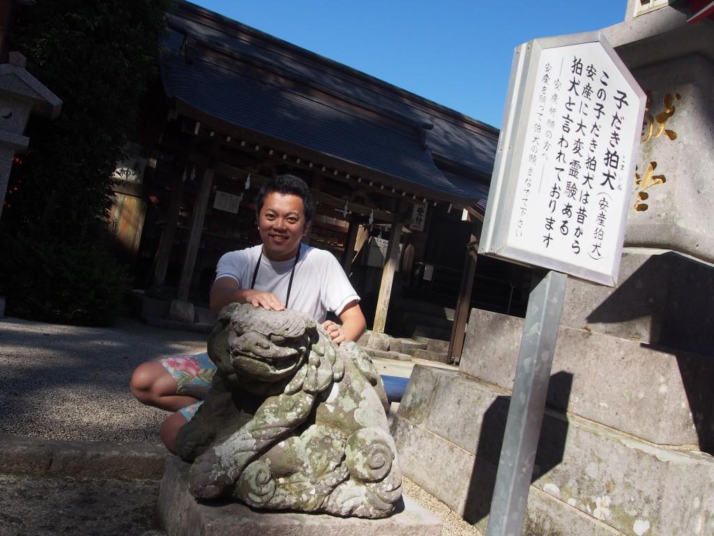 komainu hugging baby at Japanese shrine